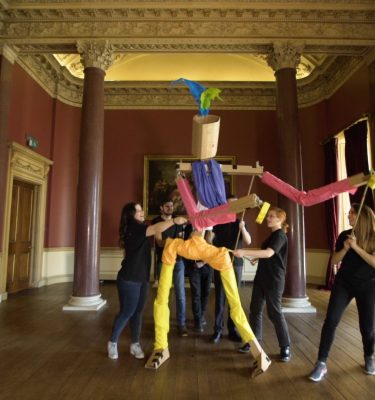 Delegates work together to move the giant puppet they created during a creative team-building experience by Orangeworks.