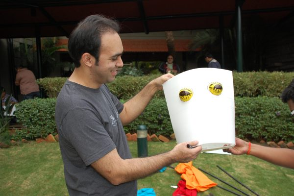 A man holding up the head part of the puppet he is creating with his team during the team building activity with Orangeworks.