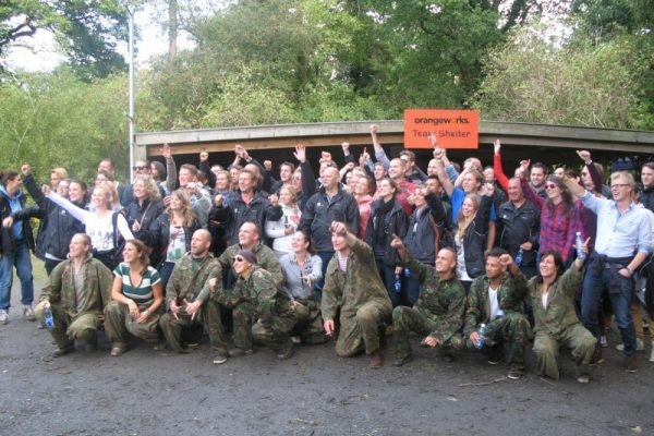 Happy team, some dressed in army clothing, smiling and cheering at Orangeworks team shelter in Carton House.