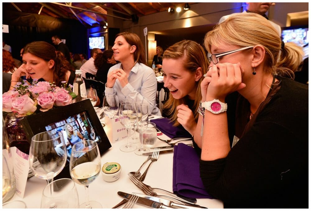 Delegates sitting at a table looking at an iPad during their corporate evening Interaction with Orangeworks.