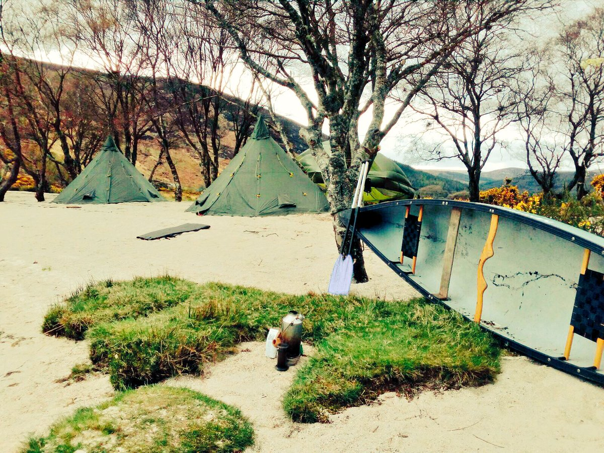 Boat and tents set up for a Bespoke Adventures with Orangeworks