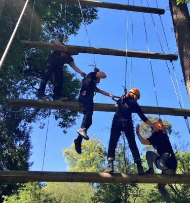 delegates working together as a team to help each other complete the jacobs ladder at carton house outdoor adventure centre.