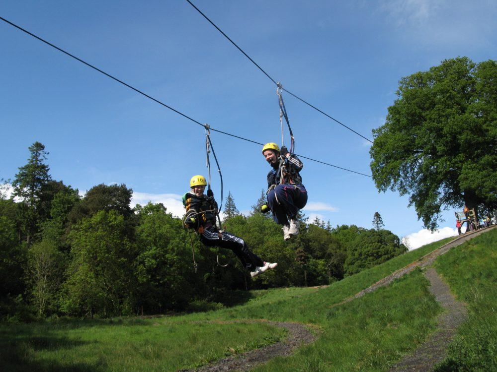 Two delegates ziplining through the forest in Carton House and Orangeworks Adventure Zone.