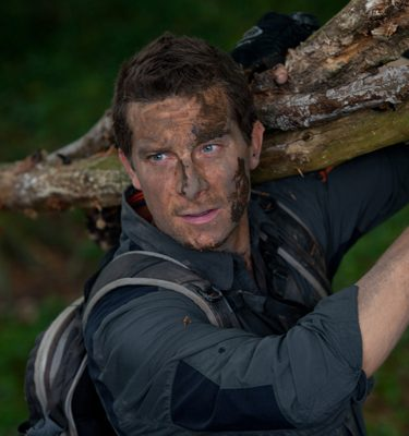 Bear Grylls holding a log, demonstrating what activities happen during the Bear Grylls survival academy.