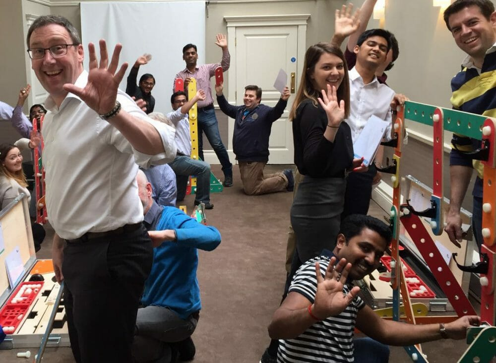 Delegates smiling with hands in the air while building their mechanical rat trap, as part of their team-building activity.