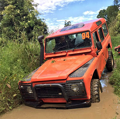 Orange land rover defender driving through a 4x4 off-road dirt track, which is part of Orangeworks off-road driving course.