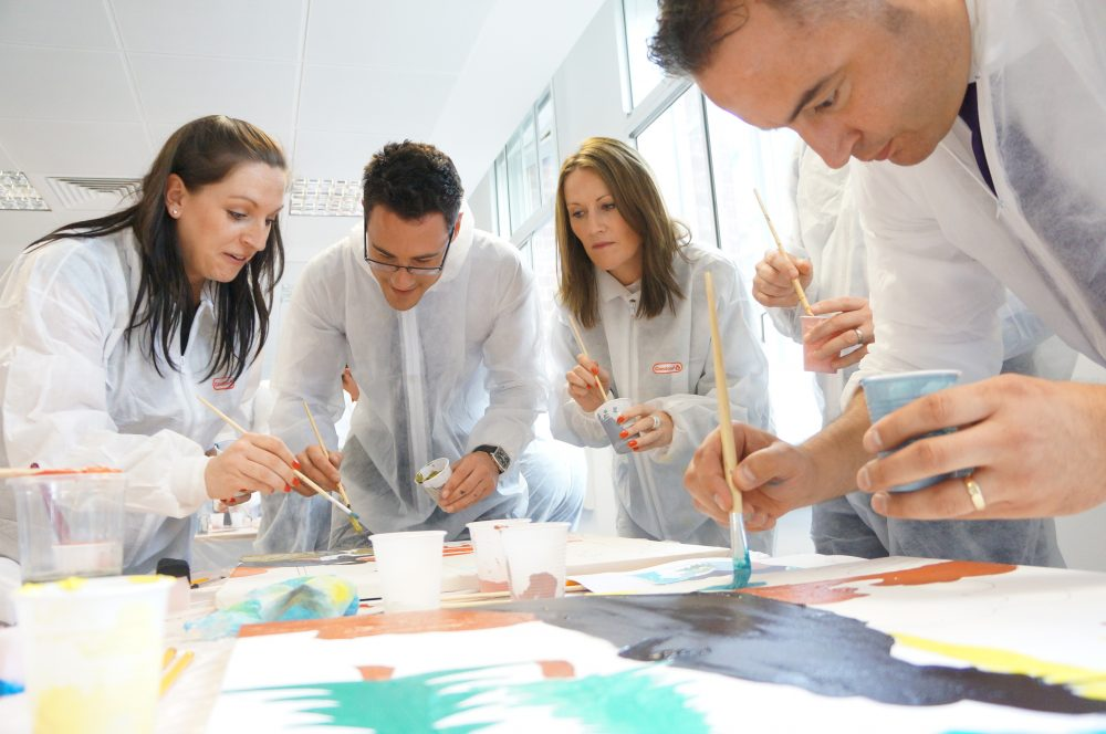 Delegates wearing white overalls painting their canvases during Big Picture, a team-building activity by Orangeworks.
