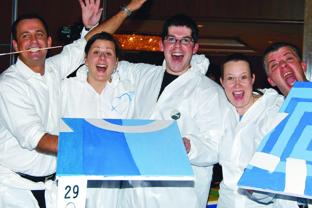 Delegates wearing white overalls holding the canvases they painted during Big Picture, a team-building activity.