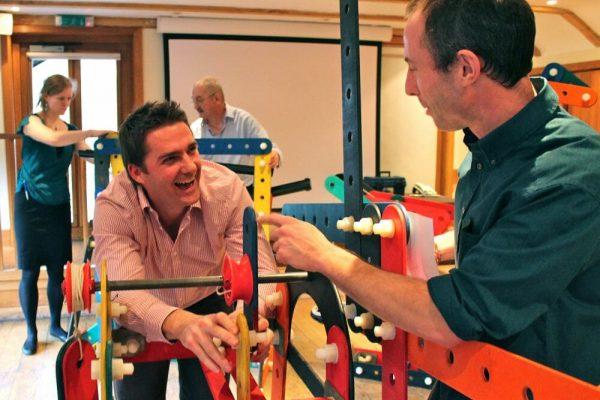 Men enjoying building rat trap together, a construction based team building activity hosted by orangeworks.