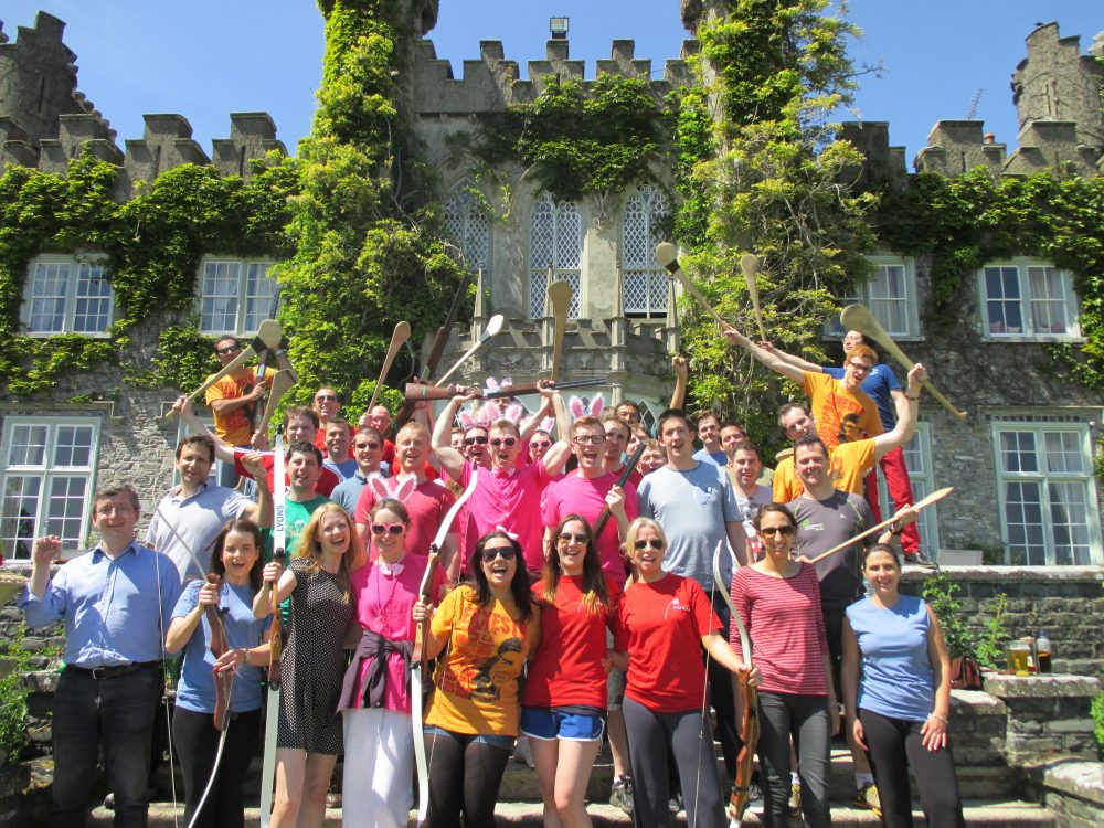 Delegates smiling and cheering after taking part in All Things Irish, a team sports activity with Orangeworks.
