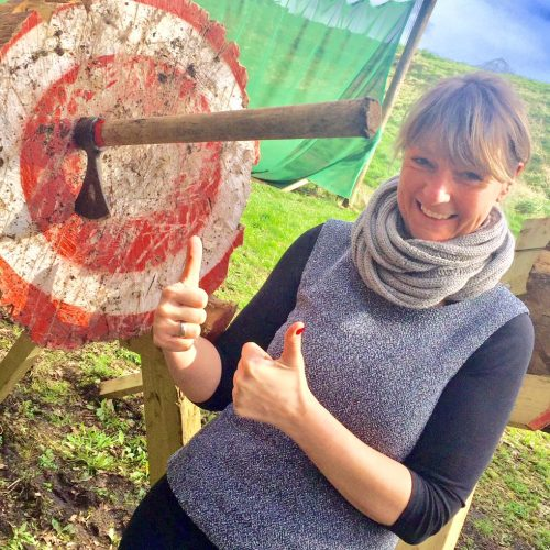 A lady giving the thumbs up with an axe and target beside her. She is enjoying an axe throwing incentive activity.