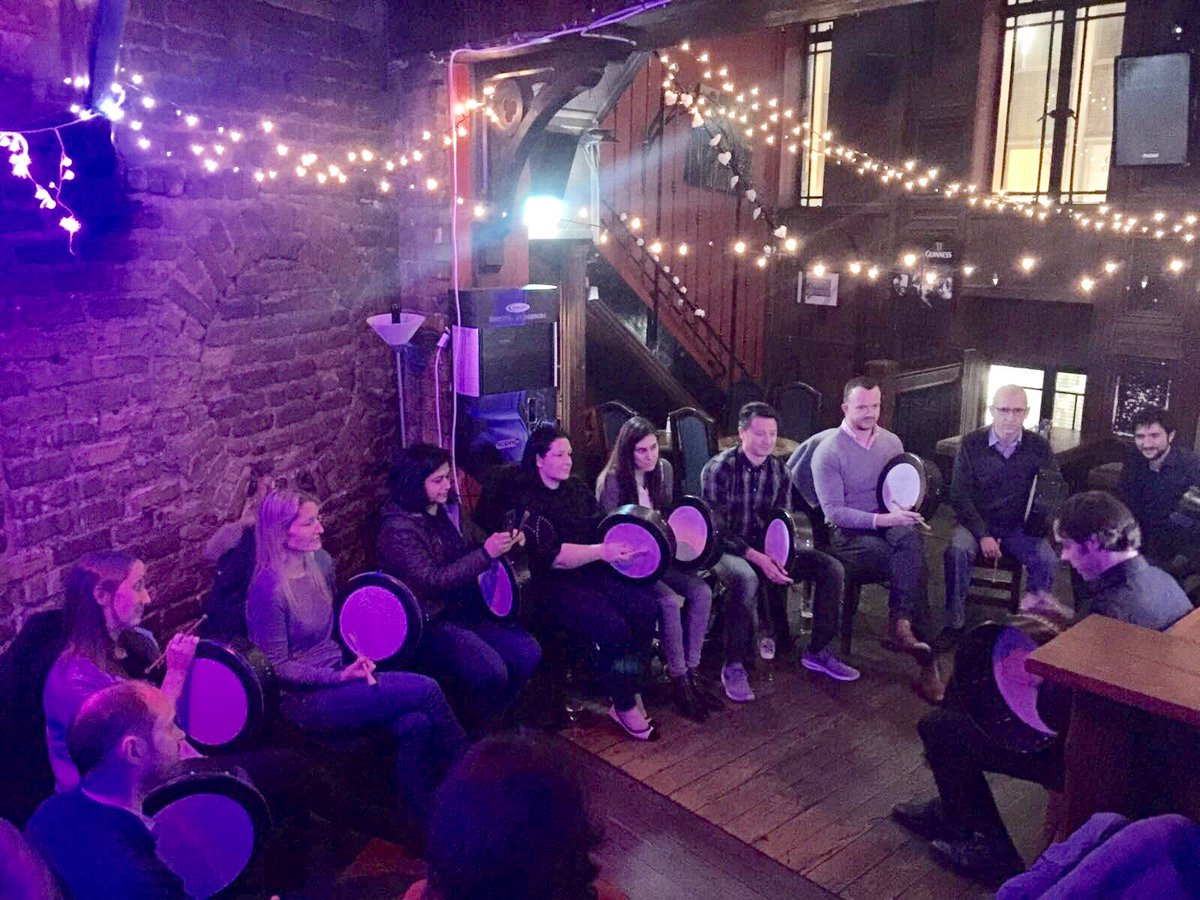 Participants of the Bodhran Workshop sitting with their bodhrans, listening to the Orangeworks instructor explain how to play