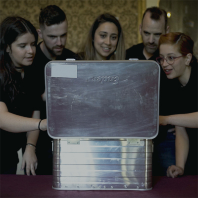 Delegates gather around a silver box in the Beat the Box escape room style team building event with Orangeworks.