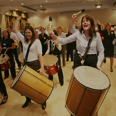 Delegates banging the samba drums & cheering during the finale of Beatswork, a musical team building activity by Orangeworks.