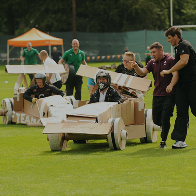 Delegates race their cardboard karts they have designed as a team.