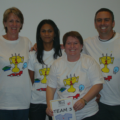 Team 3 smiling wearing the t-shirts they designed during the creative team bonding activity with Orangeworks.