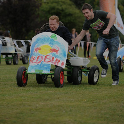 A delegate driving a go-kart with another delegate pushing him, as they compete in the finale of Thunder Races by Orangeworks.