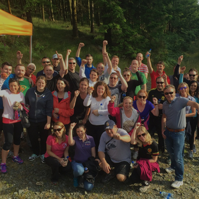 Team smiling after completing Orangeworks Xtreme Forest Adventure, an outdoor team building activity.