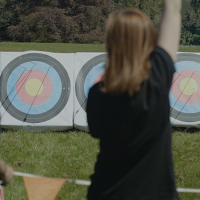 Back of girl cheering after hitting the target during Orangeworks outdoor team building activity, Archery, at Carton House.
