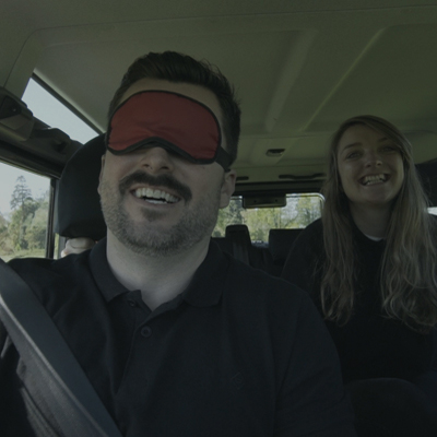 Delegates smiling with one delegate blindfolded during Orangeworks 4x4 Blindfold Driving