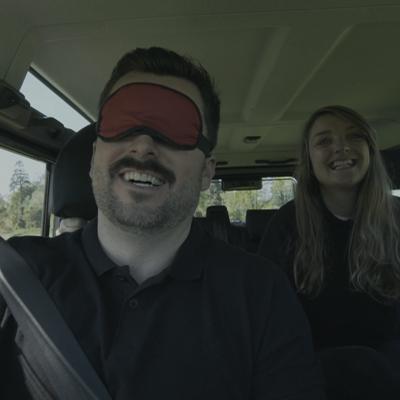 Delegates smiling with one delegate blindfolded during Orangeworks 4x4 Blindfold Driving