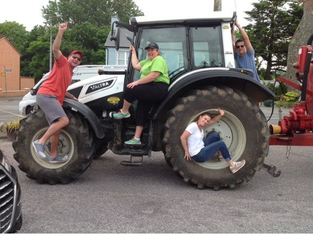 Delegates posing on a tractor as part of their photo challenges for their team building activity with Orangeworks.
