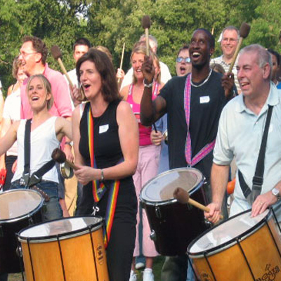 Delegates smiling, playing their instruments during the finale of Revel Music, a drumming musical team building activity.