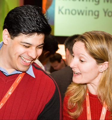 Two people smiling wearing red jumpers chatting to each other during an icebreaker conference by Orangeworks called Knowing Me Knowing You.