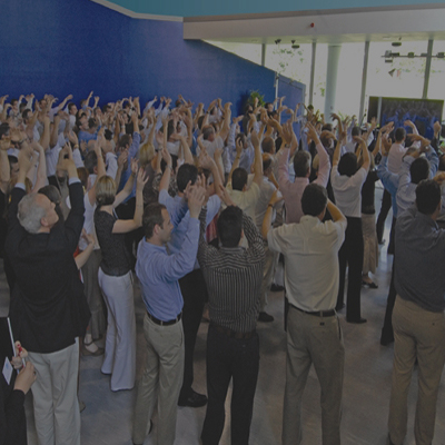 Group of delegates raising their hands in the air for One Voice, a music-themed team building experience by Orangeworks.