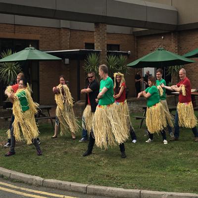 Team wearing straw hula skirts while learn to do the haka with Orangeworks
