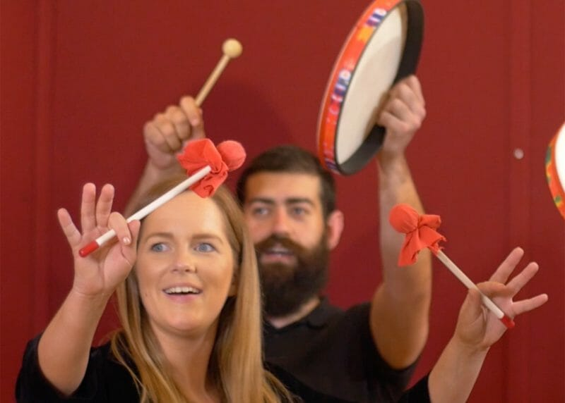 A girl holding up musical instruments while having fun during global grooves, a music team building activity by Orangeworks.