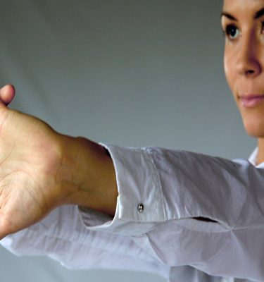 A women using one of the Head to Toe techniques of open palms stretching in front of you, she is practicing mindfulness.