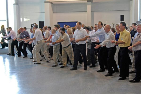 A group of male participants of One Voice, the team conference ice-breaker, standing in a line all doing the same dance move with their hands.