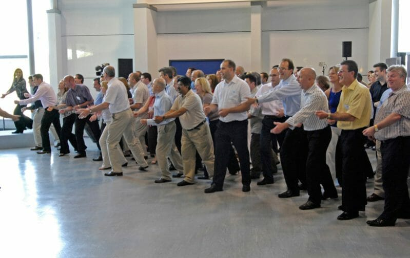 Male participants of One Voice, the team conference ice-breaker, standing in a line all doing dance move with their hands.