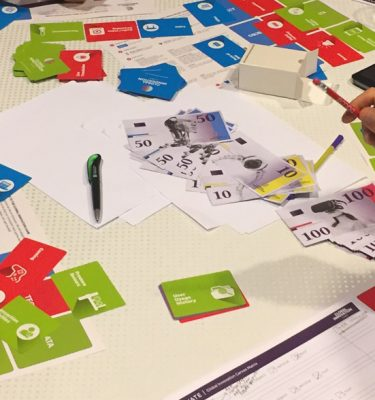 Global Innovation Game money and playing cards scattered on table
