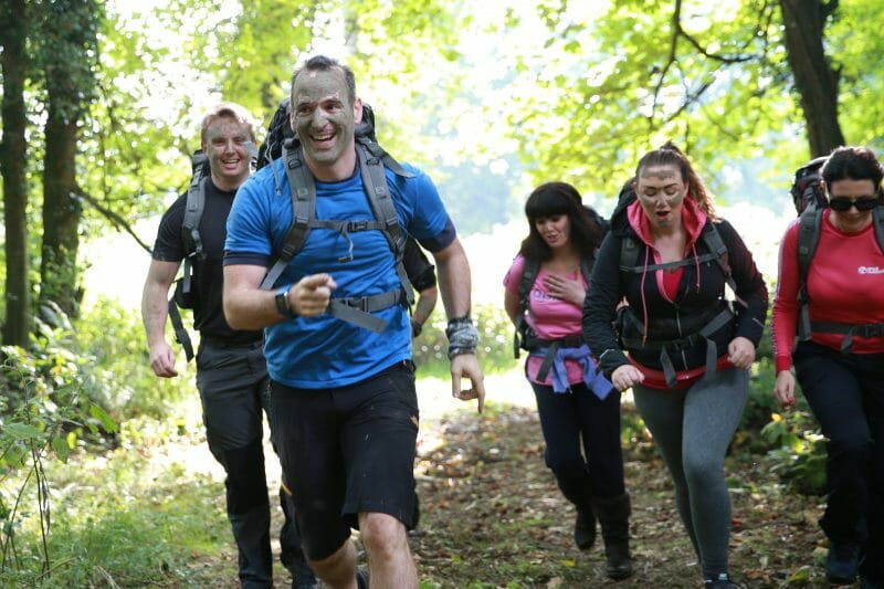 Delegates of the Bear Grylls Survival Academy, running through the forest with mud warpaint on their faces.