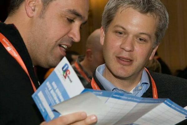 Two men looking at their question cards to see if they have anything in common during the Orangeworks icebreaker event.