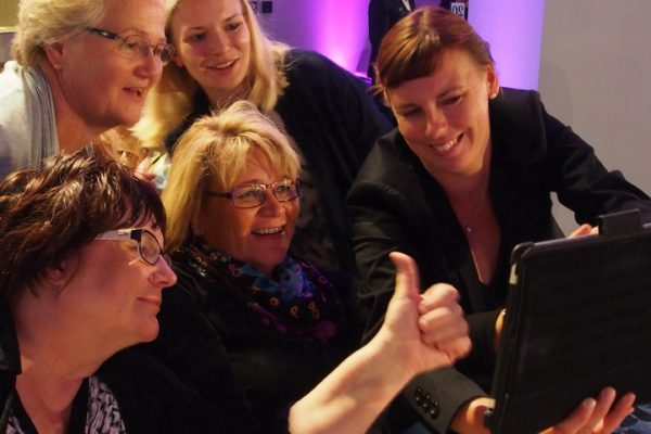 Team take a selfie on their iPad during Quickfire, a corporate evening interaction.