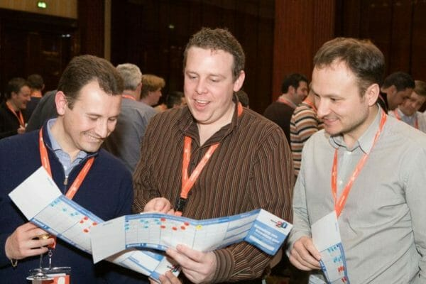 Delegates reading the questions card together during an Orangeworks icebreaker activity called Knowing Me Knowing You.