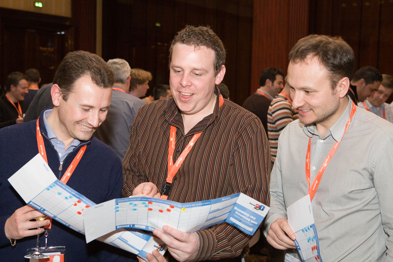 Three men chatting about their interests while reading the questions card during an Orangeworks icebreaker activity called Knowing Me Knowing You