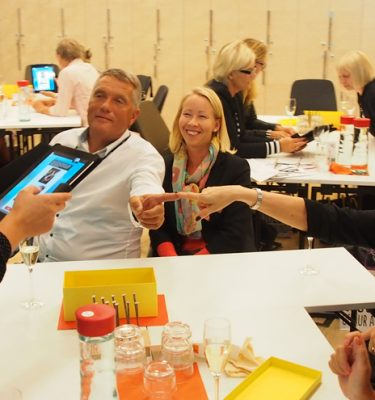 Happy delegates taking part in Quickfire - a team challenge that can be enjoyed as part of a corporate evening interaction.
