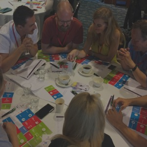 Delegates sitting around a table discussing their product idea for Global Innovation Game, a fun team building challenge.