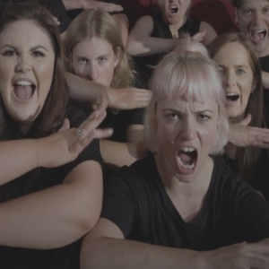 A team getting into the zone pulling funny faces as they learn the Corporate Haka together during a team bonding experience.