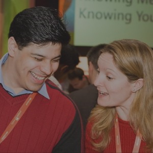 Two delegates wearing red jumpers, chatting together during Knowing Me Knowing You, a conference icebreaker by Orangeworks.
