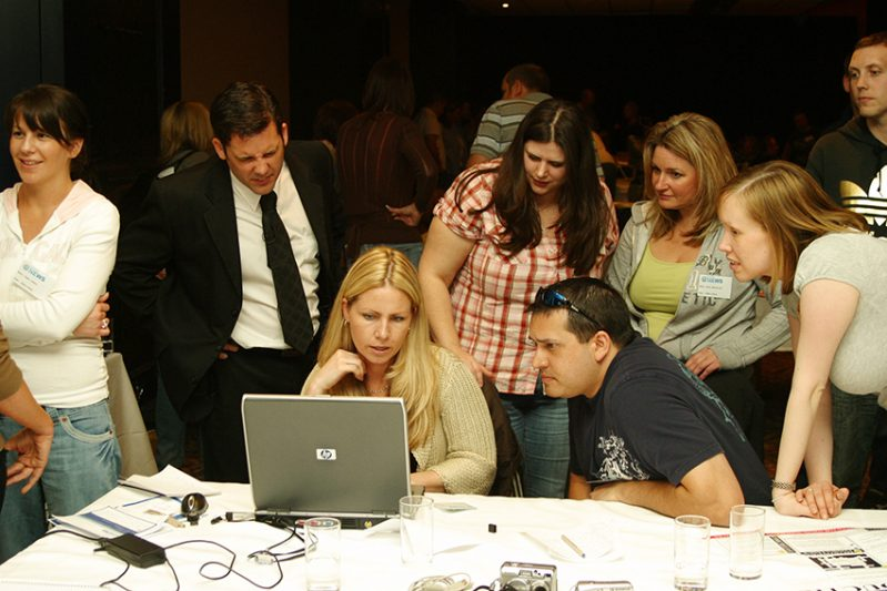Delegates gathered around a laptop deliberating how they will take on the team building challenge set by Orangeworks.