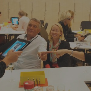 Delegates smile whilst touching index fingers as part of a Quickfire challenge, one of Orangeworks team building events.