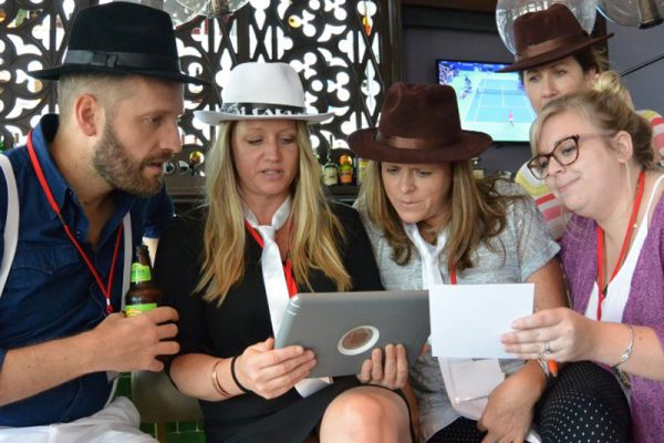 Delegates working together on a challenge on their iPad during Escape the Mob