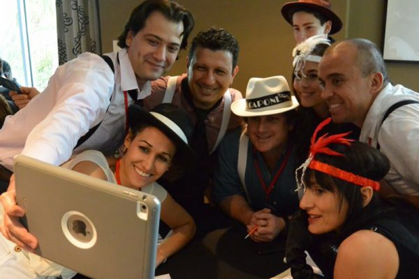 Delegates smile for a selfie on their iPad during Escape the Mob, a escape room style team challenge by Orangeworks.