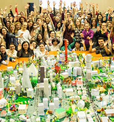 Delegates smiling and cheering behind the model city they built during their team building activity with Orangeworks