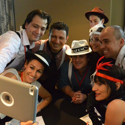 Delegates smile for a selfie in their 1920's costume, playing Escape the Mob, one of their team building activities for work.
